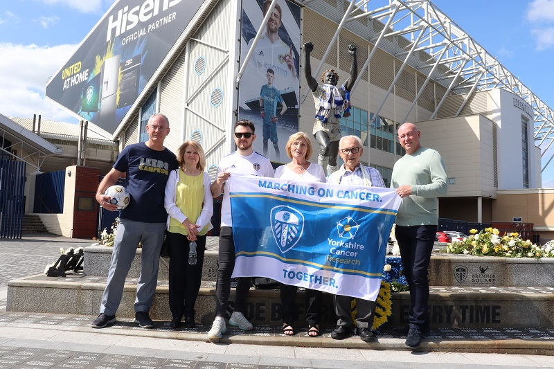 Dorothy with family outside Elland Road, holding Marching on Cancer flag