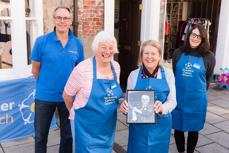 Yorkshire Cancer Research volunteers standing outside Tadcaster shop with picture of Les Emmott