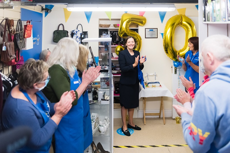 Dr Kathryn Scott presenting commemorative plaque to Yorkshire Cancer Research Tadcaster shop